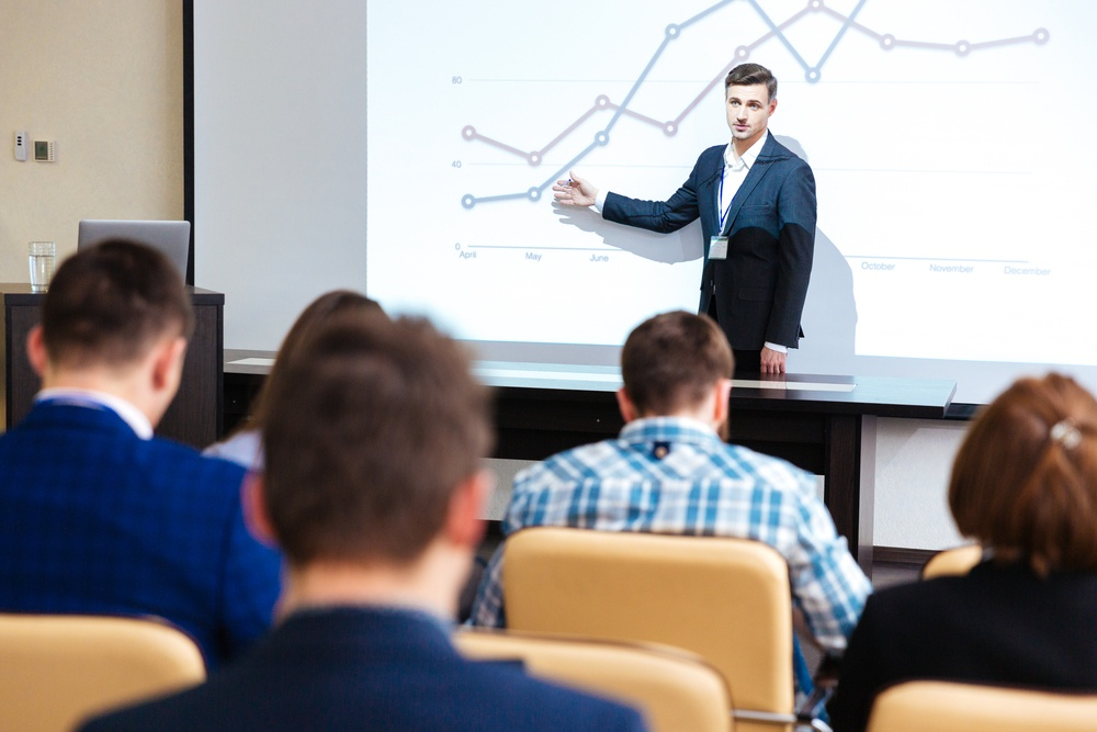 Intelligent speaker standing and lecturing at business conference in boardroom